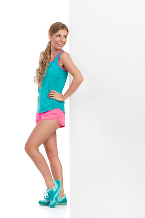 Smiling beautiful young woman in pink shorts, turquoise tank top and sneakers standing and leaning against banner and reading. Side view. Full length studio shot isolated on white.
