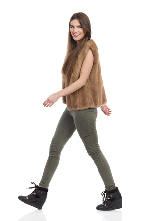 Beautiful young woman in brown fur waistcoat, khaki pants and black boots walking and looking at camera. Side view. Full length studio shot isolated on white.