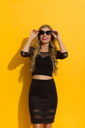 Beautiful blond young woman in sunglasses and black dress smiling and looking up. Three quarter length studio shot on yellow background.