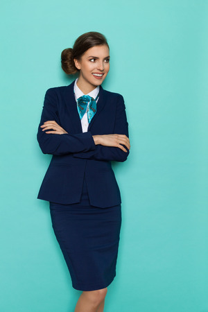 Smiling young woman in blue suit and turquoise scarf standing with arms crossed and looking away. Three quarter length studio shot on turquoise background.