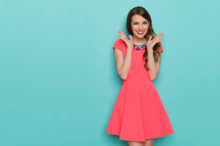 Smiling beautiful young woman in pink mini dress posing with hands on chin. Three quarter length studio shot on turquoise background. Stock Photo