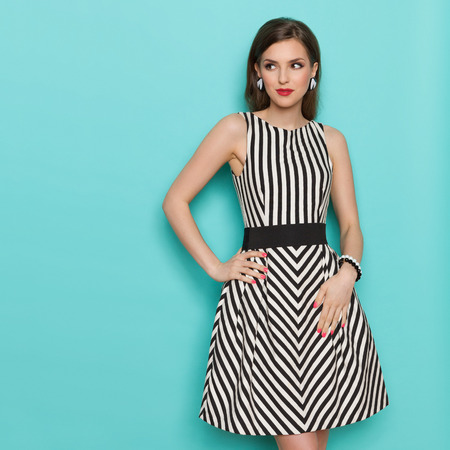 Fashion model in striped dress posing with hand on hip and looking away. Three quarter length studio shot on turquoise background. Stock Photo