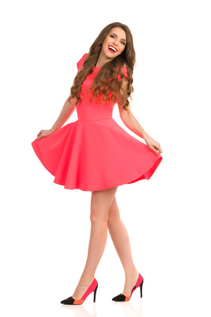 Smiling beautiful woman in pink mini dress and high heels walking and looking at camera, Full length studio shot isolated on white.