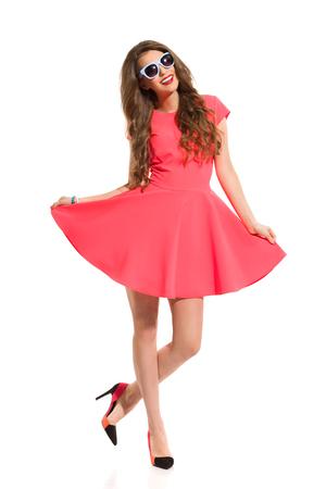Hermosa mujer joven en mini vestido rosa, gafas de sol azules y tacones de pie sobre una pierna y sonriente. Estudio de longitud completa aislado disparo en blanco. Foto de archivo