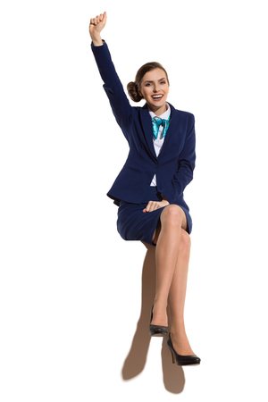 Elegant woman in blue suit and black high heels, sitting on a top with legs crossed, holding arm raised, smiling and looking at camera. Full length studio shot.