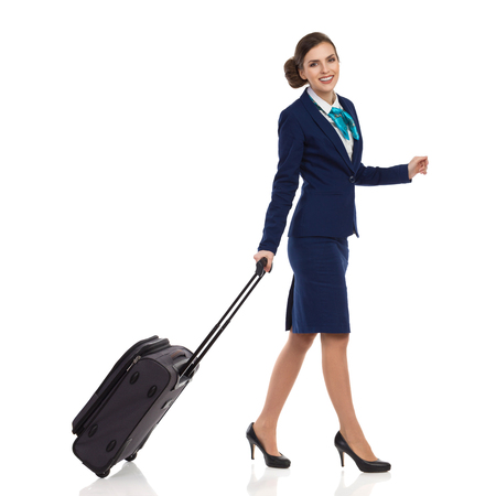 Smiling woman in blue suit and skirt walking with trolley bag and looking at camera. Full length studio shot isolated on white.