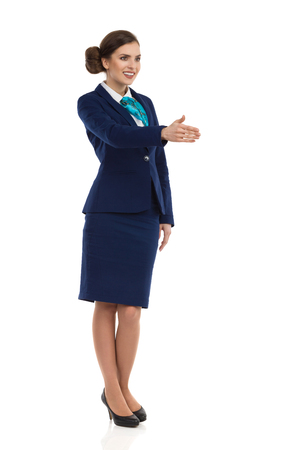 Young woman in blue formalwear and high heels, standing and giving hand for a handshake. Front side view. Full length studio shot isolated on white.