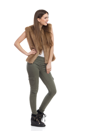 khaki: Beautiful young woman in brown fur waistcoat, khaki pants and black boots standing and looking away. Side view. Full length studio shot isolated on white.