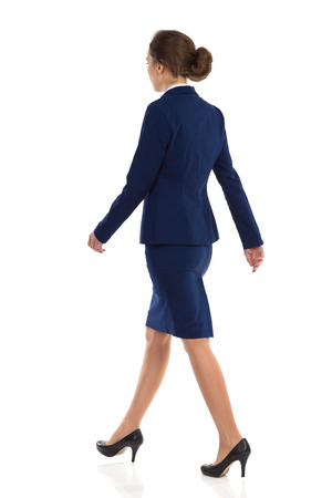 Young woman in blue suit, skirt and black high heels walking. Rear side view. Full length studio shot isolated on white. Stock Photo