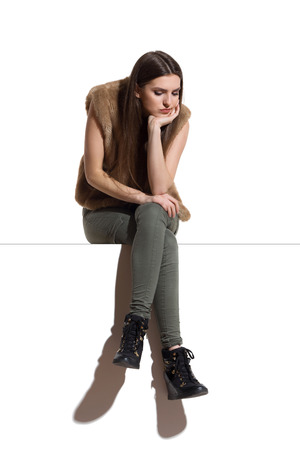 disgusted: Sad young woman in brown fur waistcoat and khaki pants sitting on a top with legs crossed and looking down. Full length studio shot.