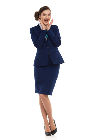 Young woman in blue formalwear and high heels, standing with head in hands and shouting. Front view. Full length studio shot isolated on white. Stock Photo