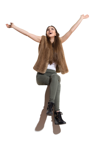 Beautiful young woman in brown fur waistcoat, khaki pants and black boots sitting on a top with arms outstretched, looking up and shouting. Full length studio shot isolated on white.