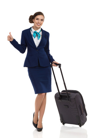 Smiling woman in blue suit and skirt standing with trolley bag, showing thumb up and looking at camera. Full length studio shot isolated on white.