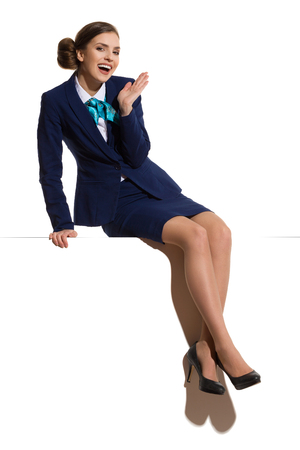 Elegant woman in blue suit and black high heels, sitting on a top, shouting and looking at camera. Full length studio shot.