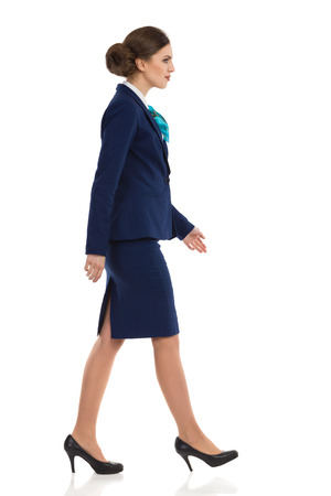 Elegant woman in blue suit, skirt and high heels walking. Side view. Full length studio shot isolated on white. Stock Photo