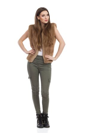 khaki: Beautiful young woman in brown fur waistcoat, khaki pants and black boots posing with hands on hip and looking at camera. Front view. Full length studio shot isolated on white. Stock Photo