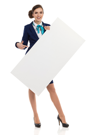 Young woman in blue formalwear and high heels, holding blank placard, pointing and smiling. Front view. Full length studio shot isolated on white.