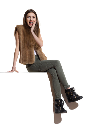 Excited beautiful young woman in brown fur waistcoat, khaki pants and black boots is sitting on a top, holding hand on chin, looking at camera and shouting. Full length studio shot isolated on white.