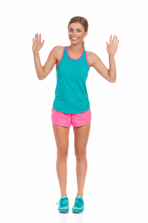 Smiling young woman in pink shorts, turquoise tank top and sneakers is standing with both hands raised, waving and looking at camera. Full length studio shot isolated on white.