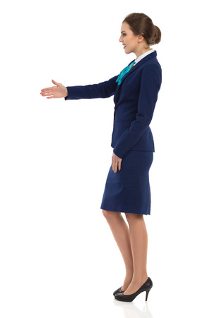 Young woman in blue formalwear and high heels is standing and giving hand for a handshake. Side view. Full length studio shot isolated on white. Stock Photo