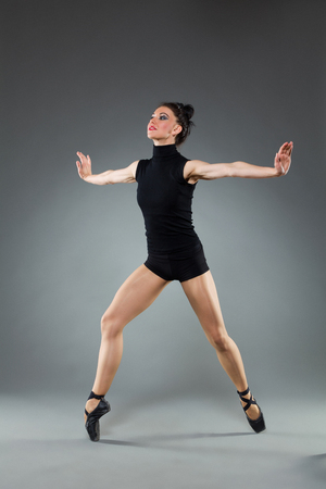 Female ballet dancer is posing with legs apart and arms outstretched. Full length studio shot on gray background. Imagens