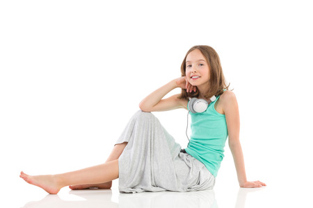 Young smiling girl with headphones on her neck is sitting on the floor. Full length studio shot isolated on white.