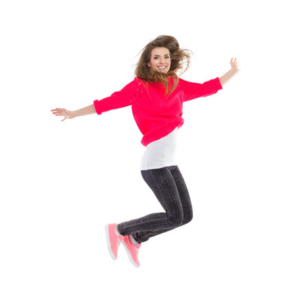 Smiling girl jumping with arms outstretched. Full length studio shot isolated on white. Imagens