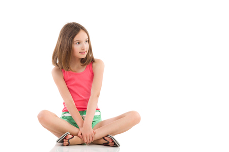 Young girl sitting on the floor with legs crossed and looking away. Full length studio shot isolated on white. Фото со стока