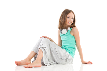 Young girl with headphones on her neck is sitting on the floor and looking away. Full length studio shot isolated on white.