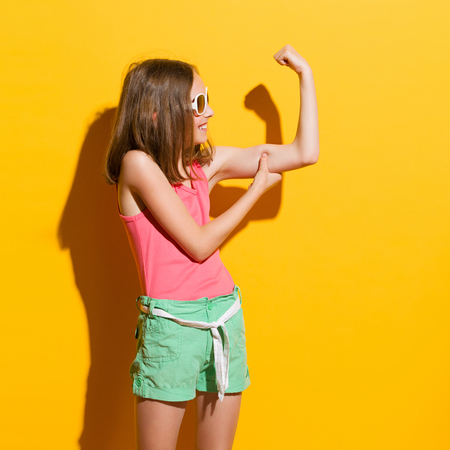 Smiling girl in sunglasses flexing biceps in the sunlight. Three quarter length studio shot on yellow background.