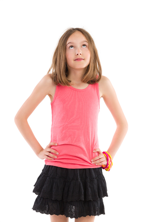 Cheerful young girl posing with hands on hip and looking up. Three quarter length studio shot isolated on white.