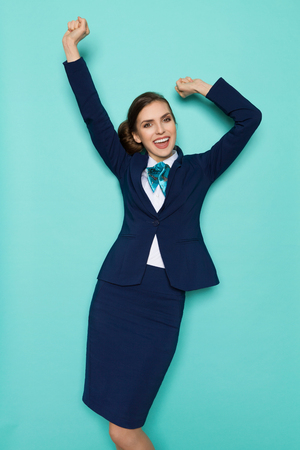 Happy young woman in blue suit and turquoise scarf is standing with arms outstretched and laughing. Three quarter length studio shot on turquoise background. Stock Photo