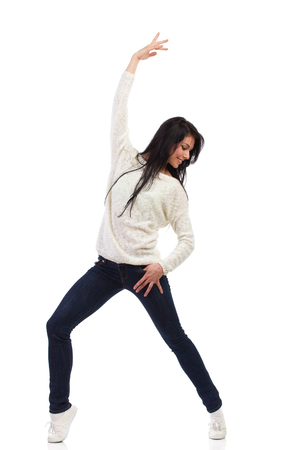 Smiling female dancing in jeans and white jersey. Full length studio shot isolated on white. Stock Photo