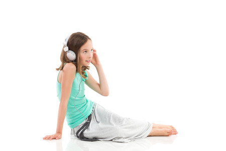 Young girl with a headphones is sitting on the floor and listening to the music. Full length studio shot isolated on white.