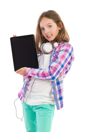 Smiling young girl holding digital tablet with blank screen. Three quarter length studio shot isolated on white.