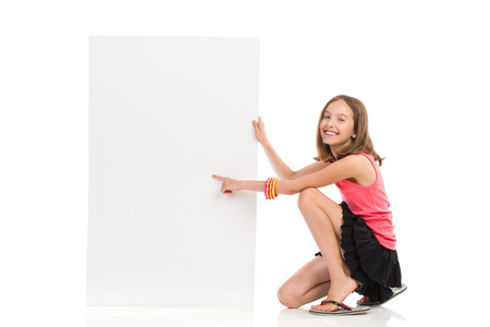 Cute girl crouch near blank banner and pointing. Full length studio shot isolated on white.