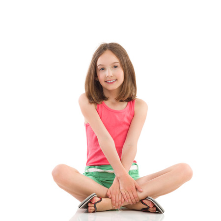 Smiling young girl posing wth legs crossed. Full length studio shot isolated on white.
