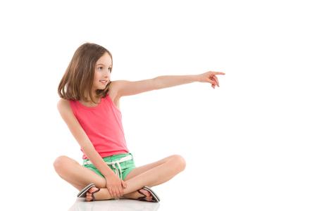 Jonge meisjeszitting op de vloer met gekruiste benen, weg kijkend en richtend. Het volledige die schot van de lengtestudio op wit wordt geïsoleerd. Stockfoto