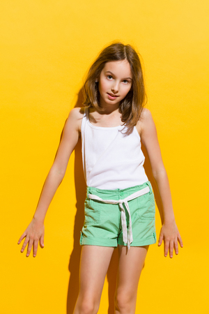 Cheerful girl posing in the sunlight. Three quarter length studio shot on yellow background.