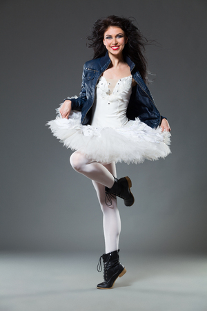 Female ballet dancer posing in a boots and leather jacket. Full length studio shot on gray background. Stock Photo