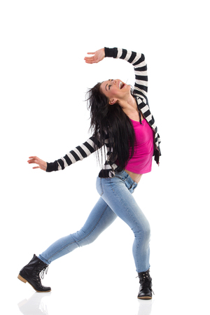 Happy female shouting with arms outstretched. Full length studio shot isolated on white.