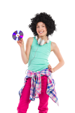 Teen girl in afro wig holding compact disc. Three quarter length studio shot isolated on white. Stock Photo