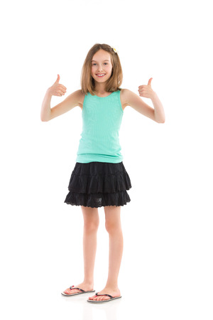 Young girl in teal shirt and black skirt showing thumbs up. Full length studio shot isolated on white.