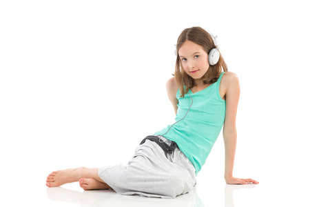 Pensive girl with headphones is sitting on the floor and listening to the music. Full length studio shot isolated on white.
