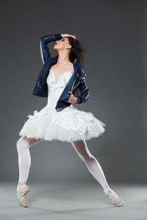 Female dancer posing in a ballet dress, pointe shoes and leather jacket. Full length studio shot on gray background.
