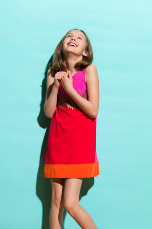 Happy day dreaming girl in mini dress looking up. Three quarter length studio shot on teal background. Imagens