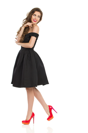 Beautiful young woman in elegant black cocktail dress and red high heels is holding hand on chin and looking away over the shoulder. Side view. Full length studio shot on isolated on white.