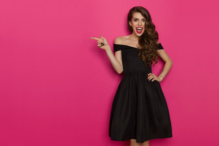 Happy beautiful young woman in elegant black cocktail dress is shouting, looking at camera and pointing. Three quarter length studio shot on pink background.
