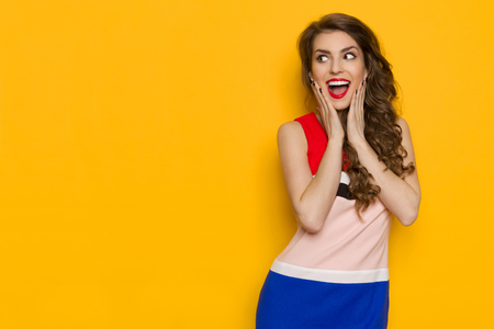 Happy beautiful young woman in colorful dress is holding head in hands, shouting and looking away at copy space. Waist up studio shot on yellow background. Banco de Imagens