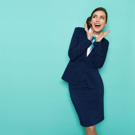 Happy young businesswoman in blue suit and turquoise scarf is standing with hands raised, shouting and looking away. Three quarter length studio shot on turquoise background. Stock Photo